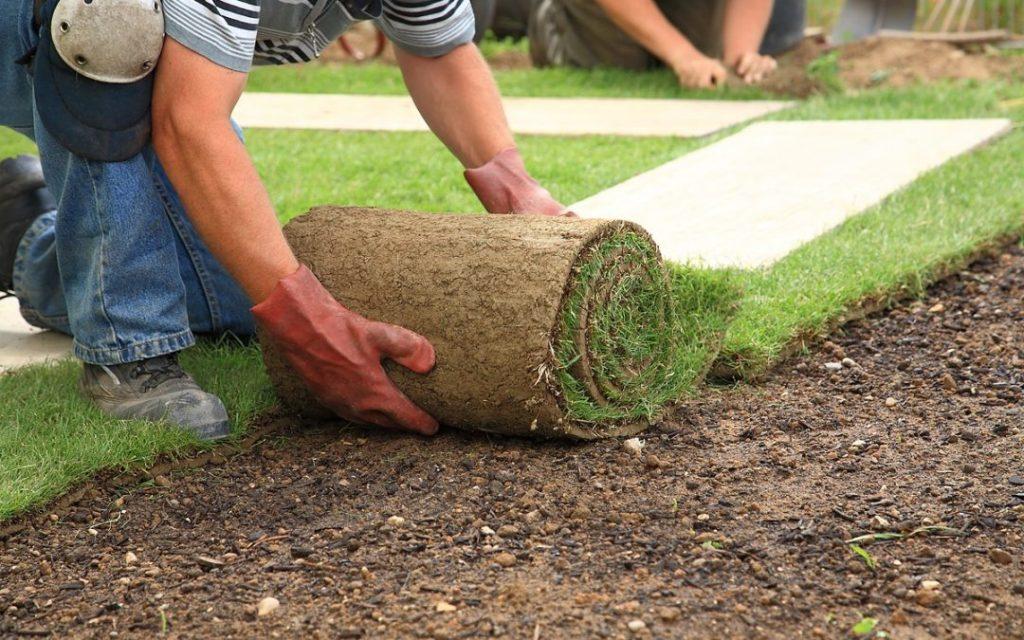 hombre instalando cesped artificial sobre tierra